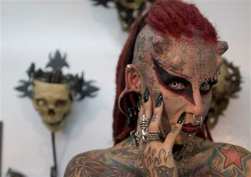 Maria Jose Cristerna poses for pictures during a press conference at a tattoo shop in Bogota, Colombia, Friday, June 3, 2011. The Mexican tattoo artist said she started to cover her body in tattoos, piercings, titanium implants and dental fangs to re-invent herself as a vampire, her reaction after suffering domestic violence. Cristerna is in Colombia to attend a tattooing international convention.   <span class=meta>(AP Photo&#47; William Fernando Martinez)</span>