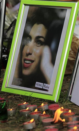 Candles are lit amongst flowers and tributes left for British singer Amy Winehouse outside her house in London, Tuesday, July 26, 2011. Amy Winehouse was found dead in her house Saturday and her funeral takes place Tuesday. &#40;AP Photo&#47;Sang Tan&#41; <span class=meta>(AP Photo&#47; Sang Tan)</span>