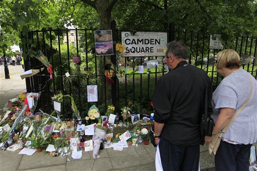 People look at flowers and tributes left for British singer Amy Winehouse outside her house in London, Tuesday, July 26, 2011. Winehouse was found dead in her house, aged 27, Saturday and her funeral takes place Tuesday. &#40;AP Photo&#47;Sang Tan&#41; <span class=meta>(AP Photo&#47; Sang Tan)</span>