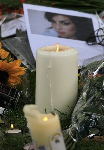 Candles are lit amongst flowers and tributes left for British singer Amy Winehouse outside her house in London, Tuesday, July 26, 2011. Amy Winehouse, 27,  was found dead in her house Saturday and her funeral takes place later Tuesday. &#40;AP Photo&#47;Sang Tan&#41; <span class=meta>(AP Photo&#47; Sang Tan)</span>