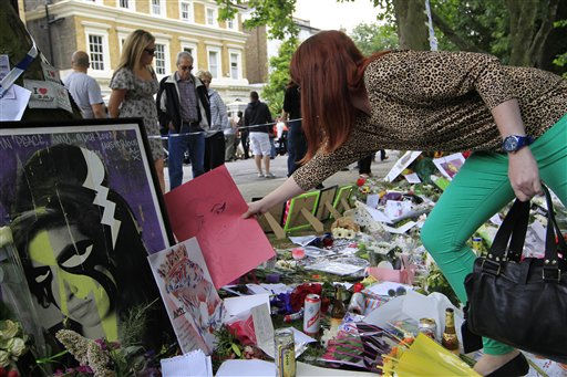 A woman places a drawing amongst the flowers and tributes left for British singer Amy Winehouse outside her house in London, Tuesday, July 26, 2011.  Winehouse, 27,  was found dead in her house Saturday and her funeral takes place later Tuesday. &#40;AP Photo&#47;Sang Tan&#41; <span class=meta>(AP Photo&#47; Sang Tan)</span>