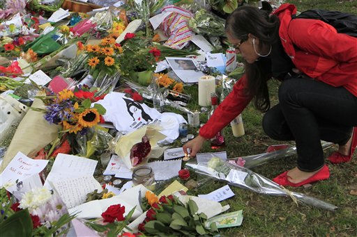 A woman lits a candle amongst the flowers and tributes left for British singer Amy Winehouse outside her house in London, Tuesday, July 26, 2011. Amy Winehouse was found dead in her house Saturday and her funeral takes place Tuesday. &#40;AP Photo&#47;Sang Tan&#41; <span class=meta>(AP Photo&#47; Sang Tan)</span>