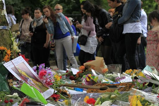 People look at flowers and tributes left for British singer Amy Winehouse outside her house in London, Tuesday, July 26, 2011. Amy Winehouse was found dead in her house Saturday and her funeral takes place Tuesday. &#40;AP Photo&#47;Sang Tan&#41; <span class=meta>(AP Photo&#47; Sang Tan)</span>