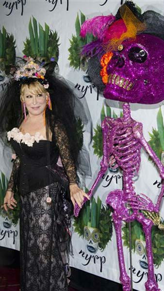 Bette Midler poses alongside a skeleton statue at her Hulaween gala benefit for the New York Restoration Project, in New York, Friday, Oct. 28, 2011. &#40;AP Photo&#47;Charles Sykes&#41; <span class=meta>(AP Photo&#47; Charles Sykes)</span>