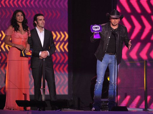 Jason Aldean, right, accepts the CMT Best Performance Of The Year award presented by Jordin Sparks, left, and Dario Franchitti at the 2012 CMT Music Awards on Wednesday, June 6, 2012 in Nashville, Tenn.