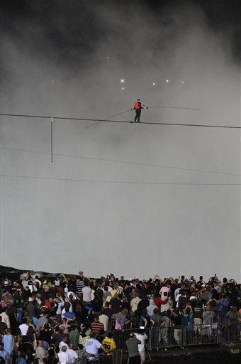 Nik Wallenda walks across Niagara Falls on a tightrope as seen from Niagara Falls, N.Y., Friday, June 15, 2012. Wallenda has finished his attempt to become the first person to walk on a tightrope 1,800 feet across the mist-fogged brink of roaring Niagara Falls. The seventh-generation member of the famed Flying Wallendas had long dreamed of pulling off the stunt, never before attempted.  &#40;AP Photo&#47;Gary Wiepert&#41; <span class=meta>(AP Photo&#47; Gary Wiepert)</span>