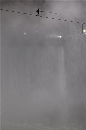 Nik Wallenda walks across Niagara Falls on a wire in Niagara Falls, N.Y., Friday, June 15, 2012. Wallenda has finished his attempt to become the first person to walk on a tightrope 1,800 feet across the mist-fogged brink of roaring Niagara Falls. The seventh-generation member of the famed Flying Wallendas had long dreamed of pulling off the stunt, never before attempted. &#40;AP Photo&#47;David Duprey&#41; <span class=meta>(AP Photo&#47; David Duprey)</span>