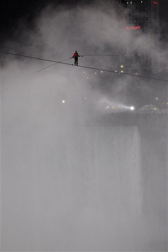 Nik Wallenda walks across Niagara Falls on a tightrope as seen from Niagara Falls, N.Y., Friday, June 15, 2012. Wallenda has finished his attempt to become the first person to walk on a tightrope 1,800 feet across the mist-fogged brink of roaring Niagara Falls. The seventh-generation member of the famed Flying Wallendas had long dreamed of pulling off the stunt, never before attempted. &#40;AP Photo&#47;David Duprey&#41; <span class=meta>(AP Photo&#47; David Duprey)</span>