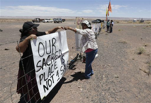 Renae Yellowhorse, left, a Navajo from Cameron, Ariz., hangs a sign as she gathers with others American Indians along highway, near Cameron, Ariz., on Sunday, June 23, 2013, to protest Florida aerialist Nik Wallenda&#39;s tightrope walk over the Little Colorado River Gorge. Wallenda planned the stunt without a safety harness on the Navajo reservation.   <span class=meta>(AP Photo&#47; Rick Bowmer)</span>