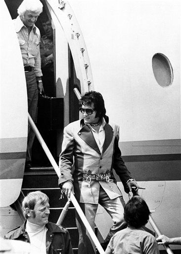 "<div class=""meta ""><span class=""caption-text "">Cigar in hand, Elvis Presley walks down the ramp after arriving in Charleston, West Virginia on July 11, 1975, for the first of three concerts in the West Virginia capital city. Elaborate security precautions kept Presley a safe distance away from the crowd which greeted him at the Kanawha Airport and at his downtown hotel. More than 18,000 tickets were sold for the concerts, one Friday at night and two Saturday. (AP Photo)</span></div>"