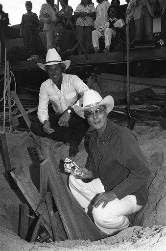 Actor Larry Hagman known to millions of television viewers as J.R.Ewing of the &#34;Dallas&#34; TV series, and co-star Steve Kanaly, background, use phony money bearing J.R.&#39;s likeness to start a bonfire on beach behind Hagman&#39;s Malibu, Calif. home on Sunday, June 30, 1980.   Hagman hosted a party for friends and cast members from the show.  <span class=meta>(AP Photo&#47; Nick Ut)</span>