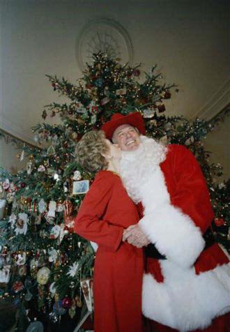 First Lady Nancy Reagan gives a kiss to actor Larry Hagman, playing Santa Claus, and who also plays &#34;J.R. Ewing&#34; in the TV series &#34;Dallas&#34; at a showing of the holiday decorations at the White House, Monday, Dec. 9, 1985 in Washington. The 20 foot Fraser Fir was supplied to the White House by Hal Johnson of Ashe Country, N.C. shown in the background.   <span class=meta>(Photo&#47;Bob Daugherty)</span>