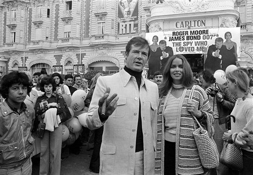 FILE - In this May 20, 1977 file photo, actor Roger Moore, alias British secret agent James Bond, is accompanied by co-star Barbara Bach as they arrive for the screening of their latest 007 feature, &#34;The Spy Who Loved Me,&#34; during the Cannes Film Festival at the French Riviera. Moore, played Bond in seven films, more than any other actor. &#40;AP Photo, File&#41; <span class=meta>(AP Photo&#47; Uncredited)</span>