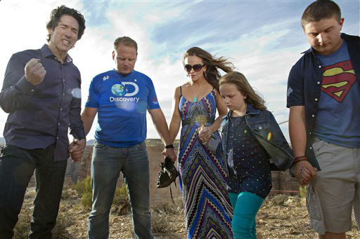 Preacher Joel Osteen, left, leads a prayer with Nik Wallenda, second from left, his wife Erendira, daughter Evita and son Yanni before Wallenda walked a 2-inch-thick steel cable that took him a quarter mile over the Little Colorado River Gorge in northeastern Arizona on Sunday, June 23, 2013. The daredevil successfully traversed the tightrope strung 1,500 feet above the chasm near the Grand Canyon in just more than 22 minutes, pausing and crouching twice as winds whipped around him and the cable swayed.  <span class=meta>(AP Photo&#47; Tiffany Brown)</span>