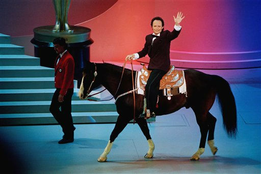 "<div class=""meta image-caption""><div class=""origin-logo origin-image ""><span></span></div><span class=""caption-text"">Billy Crystal, host of the Academy Awards, rides off stage on a horse the end of the show on Monday night, March 26, 1991 in Los Angeles. The western ""Dances with Wolves"" collected seven Oscars, including best picture. (AP Photo/Reed Saxon) (AP Photo)</span></div>"