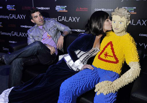 IMAGE DISTRIBUTED FOR NERDIST - NASA&#39;s Bobak Ferdowsi, looks on as Meg Turney plants one on Lego Chris Hardwick at Social Underground hosted by Nerdist Industries and comiXology at SXSW, on Sunday, March 10, 2013 in Austin.   <span class=meta>(Photo&#47;Jack Dempsey)</span>