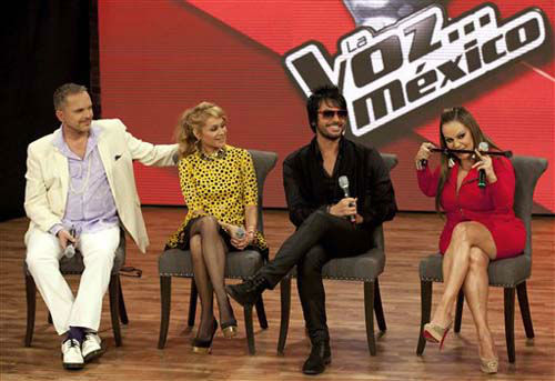Coaches for the reality show, &#34;La Voz Mexico,&#34; from left; Spanish singer Miguel Bose, Mexico&#39;s pop star Paulina Rubio, and former singer of the Chilean band La Ley, Beto Cuevas, smile as Mexican singer Jenni Rivera, using her cane as a makeshift pool stick, demostrates how she plans to intimidate her fellow coaches, at a press conference promoting the second season of the reality show music show, in Mexico City, Tuesday, Aug. 21, 2012. &#40;AP Photo&#47;Eduardo Verdugo&#41; <span class=meta>(Photo&#47;Eduardo Verdugo)</span>