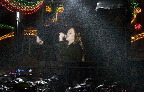 People watch mexican singer Jenni Rivera  under  heavy rain on a giant TV screen during the traditional &#34;El Grito,&#34; or shout, to kick off Independence Day celebrations at the Zocalo in Mexico City, late Saturday, Sept. 15, 2012. Mexico is marking the 202st anniversary of the &#34;Grito de Dolores,&#34; honoring the call to arms made by the priest Miguel Hidalgo in 1810 that began the struggle for independence from Spain, achieved in 1821. &#40;AP Photo&#47;Eduardo Verdugo&#41; <span class=meta>(Photo&#47;Eduardo Verdugo)</span>