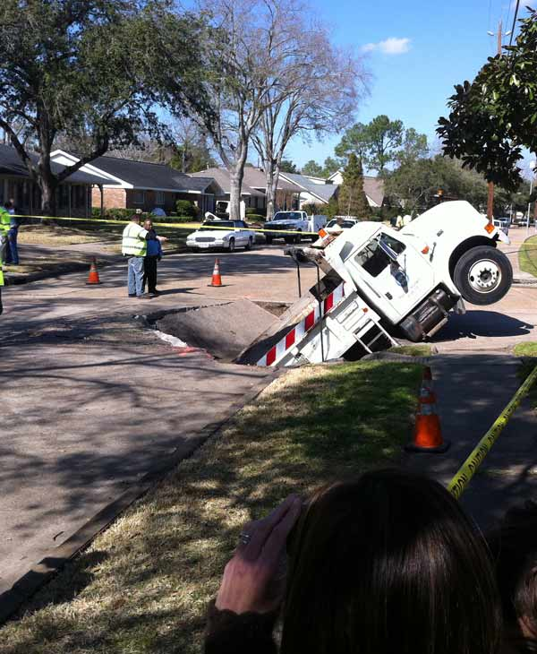 "<div class=""meta ""><span class=""caption-text "">A dump truck loaded with gravel to repair potholes ends up in a massive pot hole in southwest Houston (Photo by: Adela Uchida)</span></div>"
