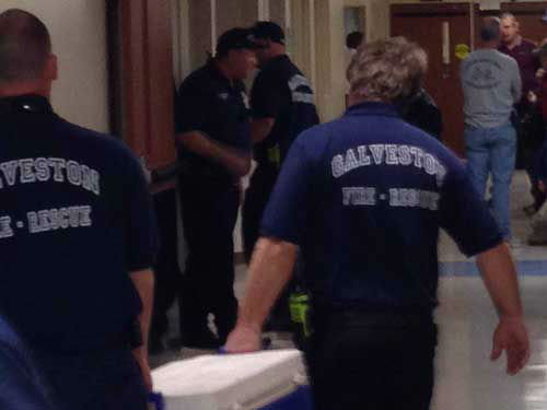 Galveston firefighters stand by in the hallways...
