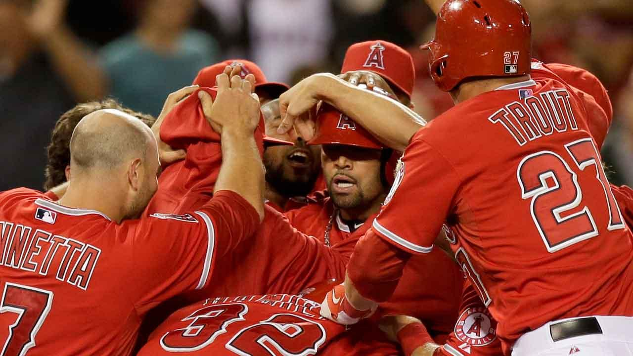 Los Angeles Angels Albert Pujols, middle, is mobbed by teammates after driving in the winning run against the Houston Astros during the ninth inning of a baseball game in Anaheim, Calif., Saturday, April 13, 2013. (AP Photo/Chris Carlson)