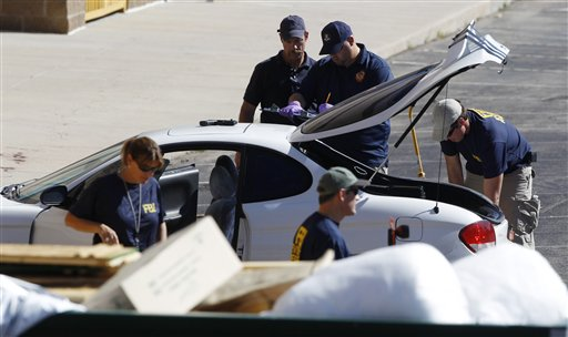 "<div class=""meta ""><span class=""caption-text "">Investigators examine a vehicle parked outside a back exit at the Century 16 movie theater east of the Aurora Mall in Aurora, Colo. on Friday, July 20, 2012. A gunman in a gas mask barged into a crowded Denver-area theater during a midnight showing of the Batman movie on Friday, hurled a gas canister and then opened fire in one of the deadliest mass shootings in recent U.S. history. (AP Photo/David Zalubowski)</span></div>"
