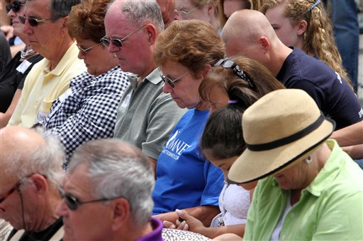 Supporters of Republican presidential candidate, former Massachusetts Gov. Mitt Romney, bow their heads during a prayer as Romney speaks about the tragic mass shooting at a movie theater in Colorado during a campaign event in Bow, N.H., Friday, July 20, 2012. (AP Photo/Jim Cole)