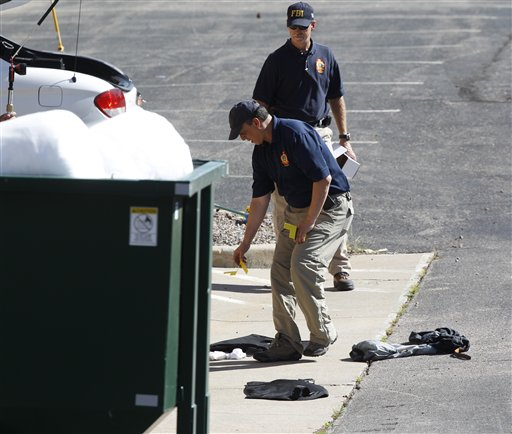 Investigators place evidence markers at the Century 16 theatre east of the Aurora Mall in Aurora, Colo., on Friday, July 20, 2012. (AP Photo/David Zalubowski)