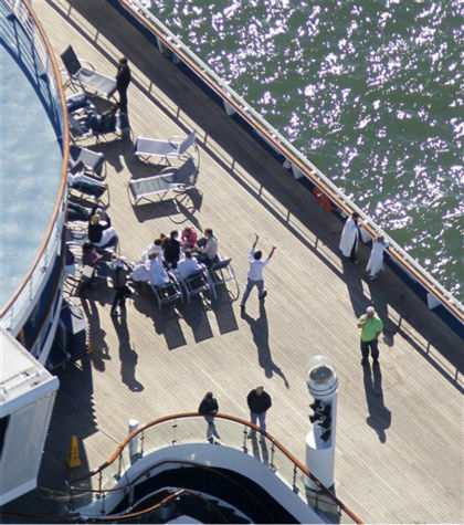 "<div class=""meta ""><span class=""caption-text "">Passengers congregate on an upper deck of the disabled Carnival Lines cruise ship Triumph as it is towed to harbor off Mobile Bay, Ala., Thursday, Feb. 14, 2013. The ship with more than 4,200 passengers and crew members has been idled for nearly a week in the Gulf of Mexico following an engine room fire.   (AP Photo/ Gerald Herbert)</span></div>"