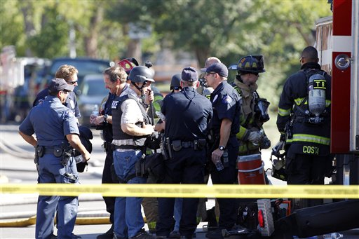 Police and firefighters gather in front of an apartment where the suspect in a shooting at a movie theatre lived in Aurora, Colo., Friday, July 20, 2012. As many as 12 people were killed and 50 injured at a shooting at the Century 16 movie theatre in Aurora, Colo., Friday, July 20, 2012. The suspect is identified as 24-year-old James Holmes. (AP Photo/Ed Andrieski)