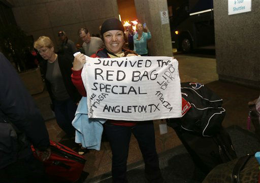 Veronica Arriaga, of Angleton, Texas, a passenger from the disabled Carnival Triumph cruise ship, holds a sign referring to the red biohazard bags used as toilets, after arriving by bus at the Hilton Riverside Hotel in New Orleans, Friday, Feb. 15, 2013. The ship had been idled for nearly a week in the Gulf of Mexico following an engine room fire.  <span class=meta>(AP photo)</span>
