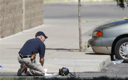 An investigator kneels next to a gas mask marked as evidence outside the Century 16 movie theater east of the Aurora Mall in Aurora, Colo. on Friday, July 20, 2012. A gunman in a gas mask barged into the crowded Denver-area theater during a midnight showing of the Batman movie on Friday, hurled a gas canister and then opened fire in one of the deadliest mass shootings in recent U.S. history. (AP Photo/David Zalubowski)