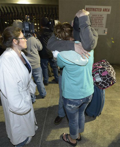 Passengers embrace after disembarking from the cruise ship Carnival Triumph in Mobile, Ala., Thursday, Feb. 14, 2013. The ship with more than 4,200 passengers and crew members has been idled for nearly a week in the Gulf of Mexico following an engine room fire.  <span class=meta>(AP photo)</span>