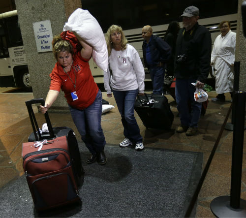 Passengers from the disabled Carnival Triumph cruise ship arrive by bus at the Hilton Riverside Hotel in New Orleans, Friday, Feb. 15, 2013. The ship had been idled for nearly a week in the Gulf of Mexico following an engine room fire.  <span class=meta>(AP photo)</span>