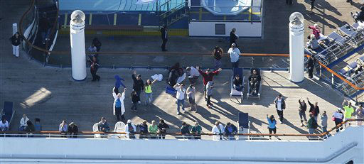 In this aerial photo, passengers congregate on an upper deck of the disabled Carnival Lines cruise ship Triumph as it is towed to harbor off Mobile Bay, Ala., Thursday, Feb. 14, 2013. The ship with more than 4,200 passengers and crew members has been idled for nearly a week in the Gulf of Mexico following an engine room fire.   <span class=meta>(AP Photo&#47; Gerald Herbert)</span>