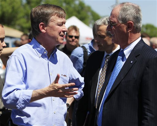 Colorado Gov. John Hickenlooper, left, confers with Steve Hogan, mayor of Aurora, Colo., after a news conference at the Century 16 theatre east of the Aurora Mall in Aurora, Colo., on Friday, July 20, 2012. A gunman in a gas mask hurled a gas canister and opened fire in the sold-out theater during a midnight showing of the new Batman movie Friday, killing 12 people and injuring 59 in one of the deadliest mass shootings in recent U.S. history. The shooter was arrested shortly after the attack, and law enforcement officials identified him as 24-year-old James Holmes. (AP Photo/David Zalubowski)