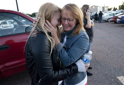 "<div class=""meta ""><span class=""caption-text "">Emma Goos, 19, hugs her mother, Judy Goos, outside Gateway High School where witnesses were brought for questioning Friday, July 20, 2012, in Aurora, Colo. Emma was in the third row of the theater of the new Batman movie when the shooter entered. She helped apply pressure to a man's head who was injured. (AP Photo/Barry Gutierrez)</span></div>"