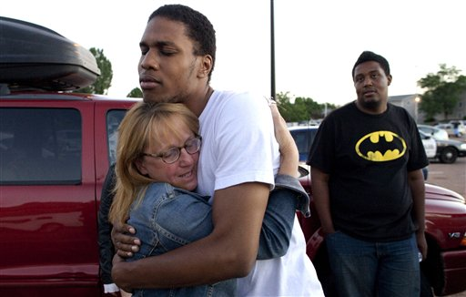 "Judy Goos, left, hugs her daughters friend, Isaiah Bow, 20, an eyewitnesses, as Terrell Wallin, 20, right, looks on, outside Gateway High School where witnesses were brought for questioning after a gunman opened fire at the midnight premiere of the ""Dark Knight Rises""movie Friday, July 20, 2012 in Aurora. After fleeing the theater, Bow returned to find his girlfriend who turned out to be safe. ""Very stupid I know, But I didn't want to leave her in there,"" says Bow. (AP Photo/Barry Gutierrez)"