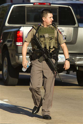 A heavily armed policeman walks along at the Lone Star College North Harris campus  Tuesday Jan.  22, 2013 in Houston.   A shooting at the Texas community college wounded three people Tuesday and sent some students fleeing for safety while others with medical training helped tend the wounded.   <span class=meta>(AP Photo&#47; Patric Schneider)</span>