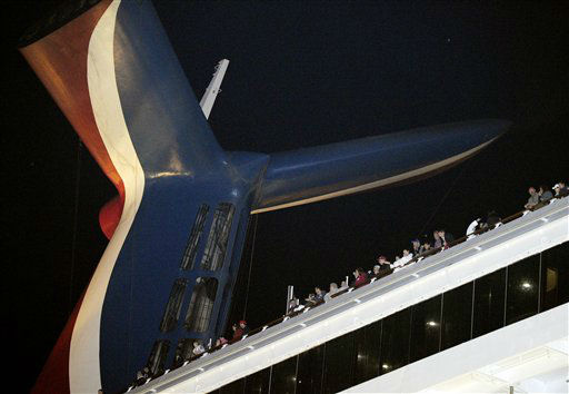 People watch from their balconies aboard the Carnival Triumph after it was towed to the cruise terminal in Mobile, Ala., Thursday, Feb. 14, 2013. The ship with more than 4,200 passengers and crew members idled for nearly a week in the Gulf of Mexico following an engine room fire. <span class=meta>(AP photo)</span>