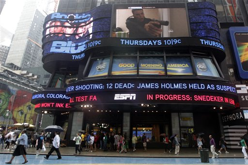 "The ABC news ticker in Times Square displays news on the mass shooting at a Colorado movie theater, Friday, July 20, 2012 in New York. A gunman in a gas mask barged into a crowded Denver-area theater during a midnight premiere of the Batman movie on Friday, hurled a gas canister and then opened fire, killing 12 people and injuring at least 50 others in one of the deadliest mass shootings in recent U.S. history. NYPD commissioner Ray Kelly said the department was providing the extra security at theaters ""as a precaution against copycats and to raise the comfort levels among movie patrons."" (AP Photo/Mary Altaffer)"