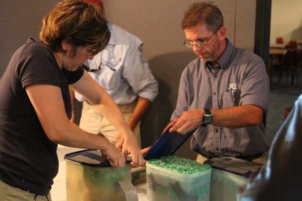 Amy Borgens of Texas Historical Commission and Christopher Horrell of the Bureau of Safety and Environmental Enforcement prepare display table with items from the wreckage of an early 19th century shipwreck recently documented and partially excavated in the Gulf of Mexico in more than 4,300 feet of water.  The wreck is one of three sites investigated by scientists from the Bureau of Ocean Energy Management, the National Oceanic and Atmospheric Administration, the Bureau of Safety and Environmental Enforcement, the Texas Historical Commission, and the Meadows Center for Water and the Environment at Texas State University.  The project was funded by donations and sponsorships arranged by the Meadows Center, and conducted in partnership with the Ocean Exploration Trust at the University of Rhode Island on board the Exploration Vessel Nautilus. <span class=meta>(Moody Gardens Cameron Palmer)</span>
