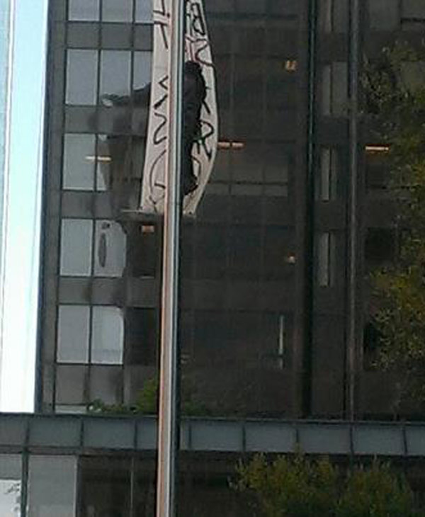 "<div class=""meta ""><span class=""caption-text "">A protestor was taken into police custody after he climbed a pole in downtown Houston and put a banner. (iWitness photo)</span></div>"