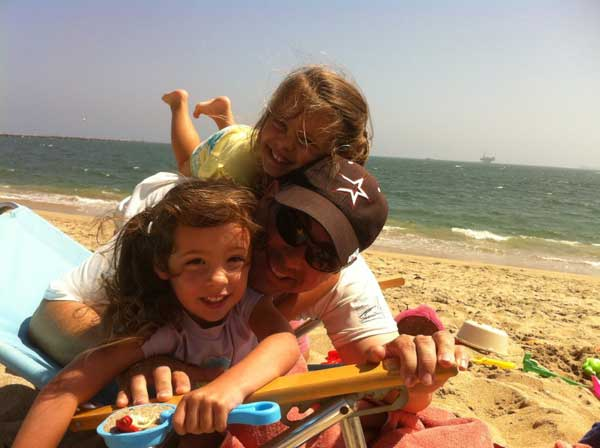 Reporter and Father Kevin Quinn and twins on the beach