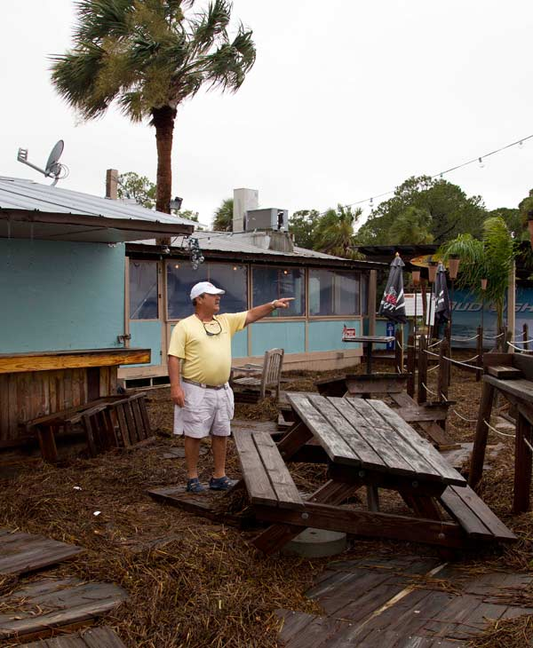 Mark Mitchell surveys the damage to the Posey's Dockside Cafe at the Rock Landing Marina in Panacea, Fla., Tuesday, June 26, 2012. High winds and heavy rains spawned by the approaching Tropical Storm Debby caused the damage. (AP Photo/Dave Martin)