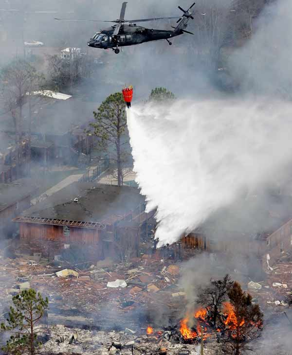 An aerial photo shows a helicopter dropping water on burning debris from Hurricane Katrina, Wednesday, Aug. 31, 2005, in Long Beach, Miss. (AP Photo/David J. Phillip)
