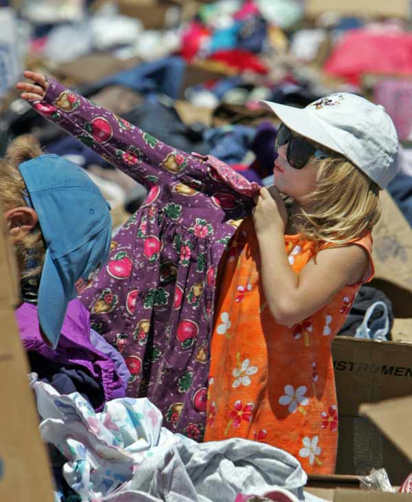 Five-year-old Shelby Batts tries on a dress at a clothing distribution center while her father Anthony, left, looks for clothes for his other two daughters in Gulfport, Miss., on Wednesday, Sept. 7, 2005. Shelby also found her hat and sunglasses at the donation area. (AP Photo/John Bazemore)