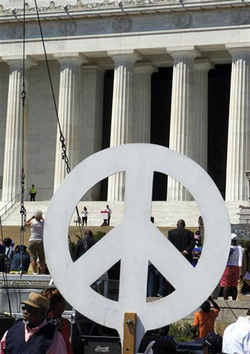 "<div class=""meta ""><span class=""caption-text "">One of the speakers at a rally to commemorate the 50th anniversary of the 1963 March on Washington on the steps of the Lincoln Memorial is seen through a peace sign on Saturday, Aug. 24, 2013, in Washington. (AP Photo/Jon Elswick) (Photo/Jon Elswick)</span></div>"