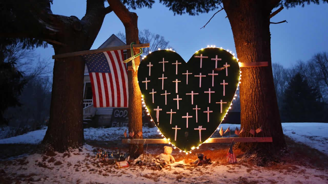 A makeshift memorial with crosses for the victims of the Sandy Hook massacre stands outside a home in Newtown, Conn., Saturday, Dec. 14, 2013, the one-year anniversary of the shootings