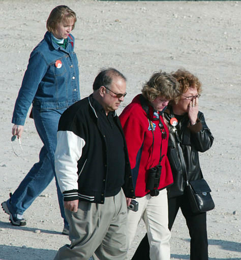 Spectators console each other after hearing news of the disintegration of the Space Shuttle Columbia over Texas while leaving the Space Shuttle landing facility on Saturday, Feb. 1, 2003 at the Kennedy Space Center in Cape Canaveral, Fla. Space shuttle Columbia apparently disintegrated in flames over Texas on Saturday minutes before it was to land in Florida. TV video showed what appeared to be falling debris, as NASA declared an emergency and warned residents to beware of falling objects.  &#40;AP Photo&#47;Terry Renna&#41; <span class=meta>(AP Photo&#47; TERRY RENNA)</span>